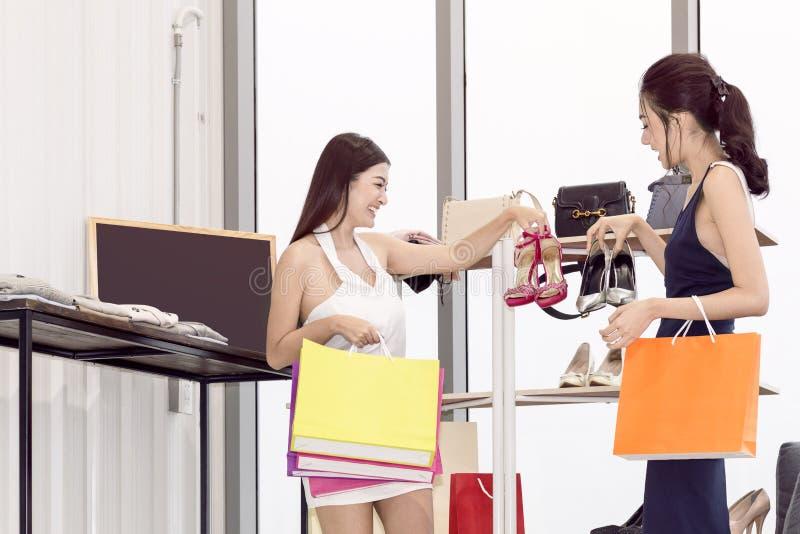 Giovani bei donna ed amico con godere del sacchetto della spesa fotografia stock libera da diritti