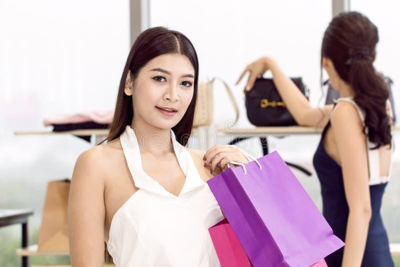 Giovani bei donna ed amico con godere del sacchetto della spesa immagine stock libera da diritti