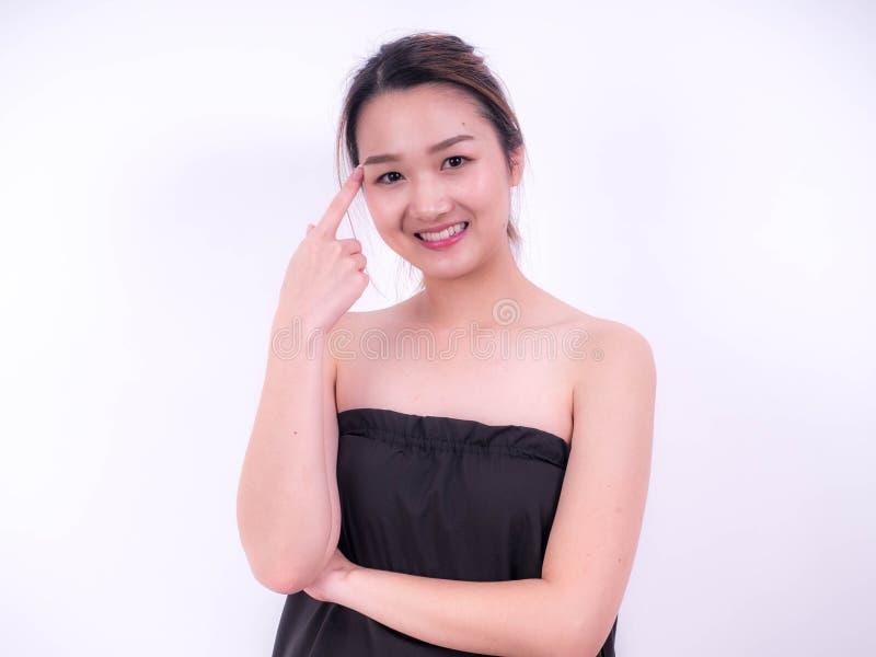 Giovani bei sorriso e punto asiatici della donna sulla sua testa, isolata sopra fondo bianco trucco naturale, terapia della STAZI fotografia stock libera da diritti