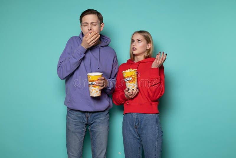 Giovani belle coppie in abbigliamento casual che mangia popcorn, alesato durante il film noioso immagini stock