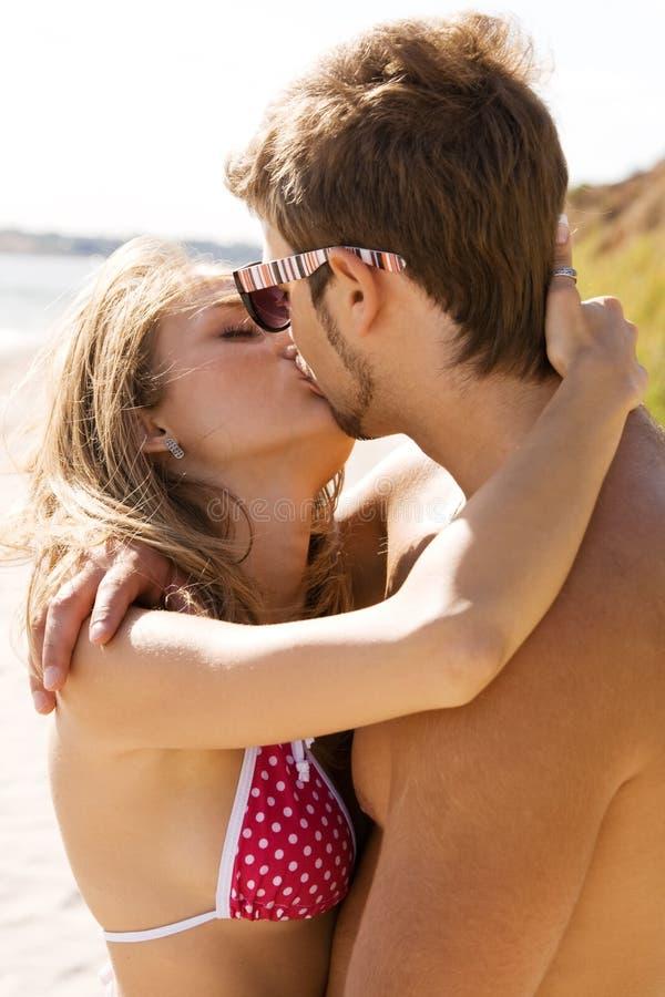 Giovani belle coppie che baciano sulla spiaggia fotografia stock libera da diritti