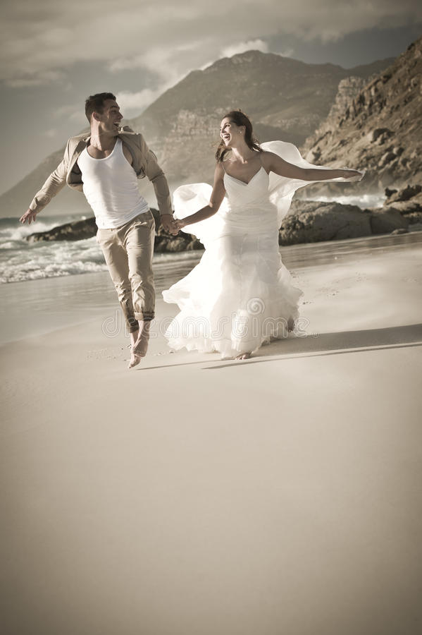 Giovani belle coppie che corrono allegro attraverso la spiaggia fotografia stock