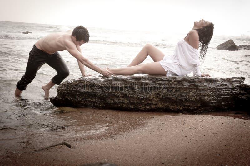 Giovani belle coppie che flirtano alla spiaggia fotografia stock libera da diritti