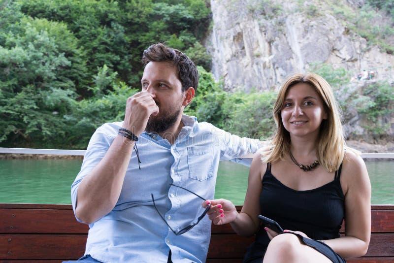 Giovani belle coppie che godono di un'escursione in una piccola barca in un canyon Ragazzo con capelli neri e la ragazza caucasic fotografia stock libera da diritti
