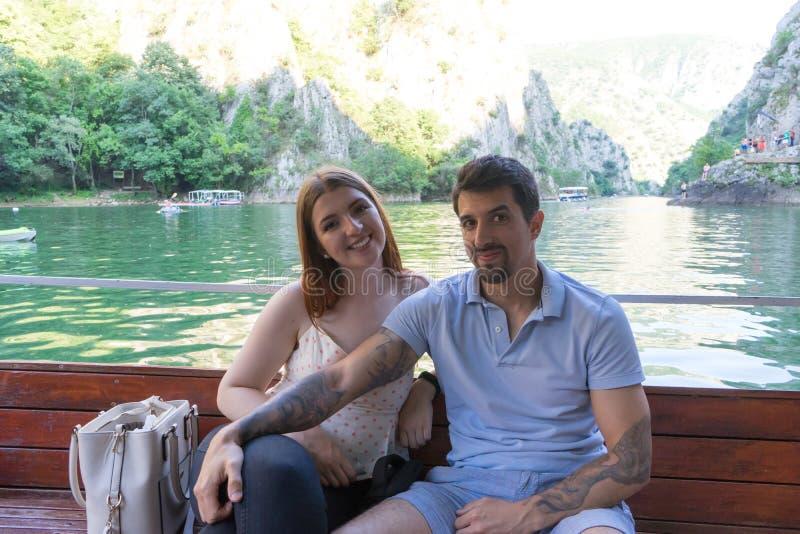 Giovani belle coppie che godono di un'escursione in una piccola barca in un canyon Ragazzo con i tatuaggi e ragazza caucasica bia fotografia stock