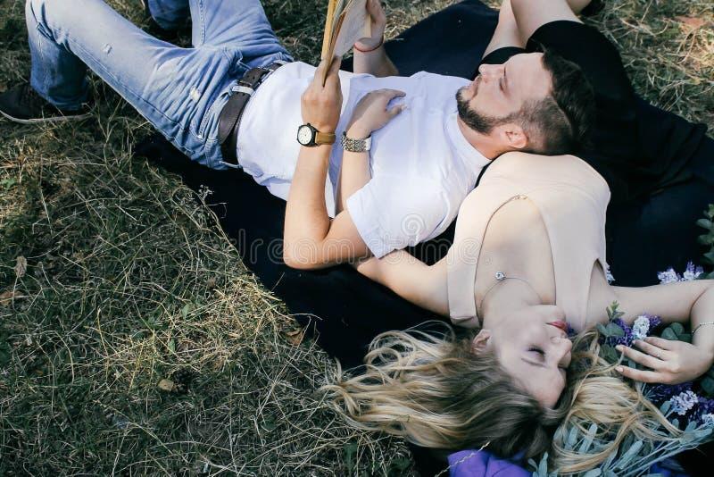 Giovani belle coppie che riposano nella foresta fotografia stock