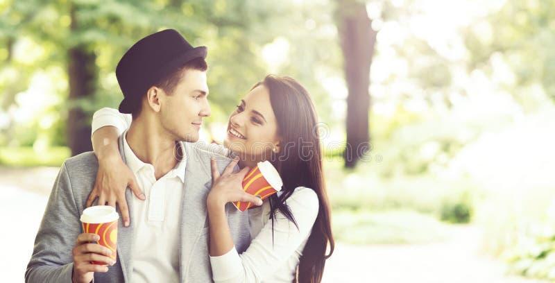 Giovani belle coppie dei pantaloni a vita bassa: abbracciando nel parco fotografie stock libere da diritti
