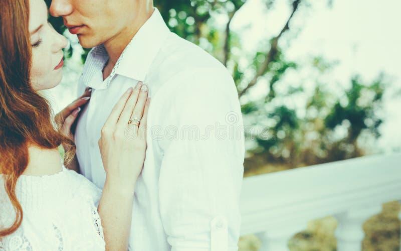 Giovani belle coppie nell'abbraccio di amore nel parco di estate Godere insieme del concetto romantico immagini stock