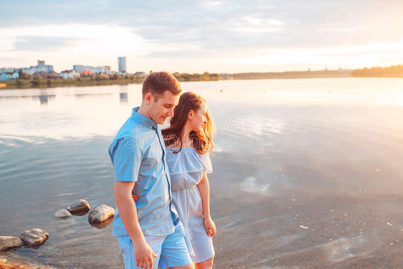 Giovani belle coppie nell'amore che resta e che bacia sulla spiaggia sul tramonto Colori pieni di sole morbidi fotografia stock