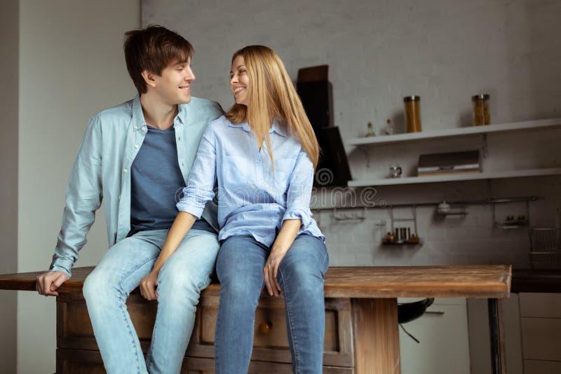 Giovani belle coppie in panno blu del denim che si siede nella cucina immagine stock libera da diritti