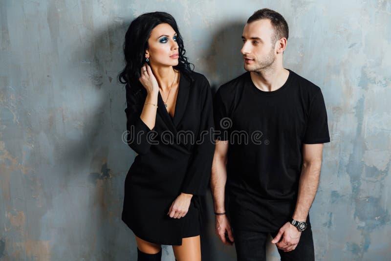 Giovani belle coppie splendide alla moda, contro il sottotetto grigio della parete nello studio o a casa fotografia stock libera da diritti