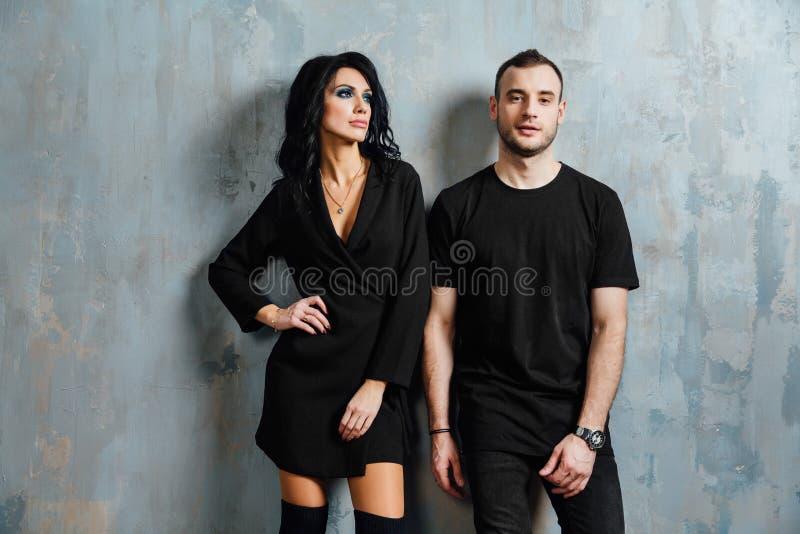 Giovani belle coppie splendide alla moda, contro il sottotetto grigio della parete nello studio o a casa immagini stock libere da diritti