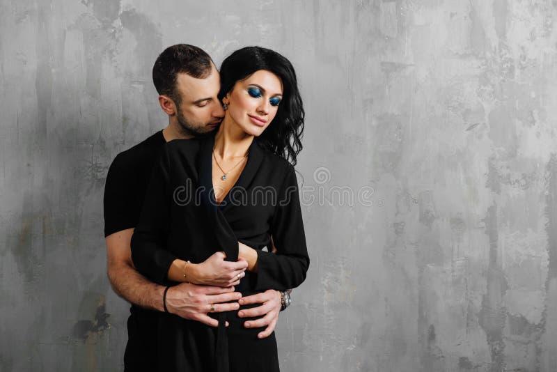 Giovani belle coppie splendide alla moda, contro il sottotetto grigio della parete nello studio o a casa immagini stock