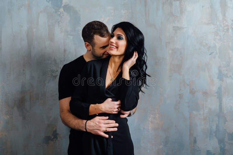 Giovani belle coppie splendide alla moda, contro il sottotetto grigio della parete nello studio o a casa immagine stock