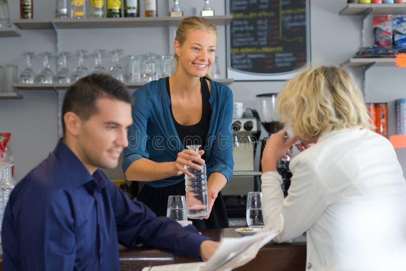 Giovani bevande felici del servizio della cameriera al banco fotografia stock