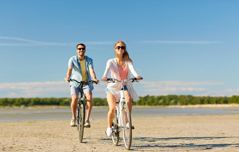 Giovani biciclette felici di guida delle coppie alla spiaggia immagini stock libere da diritti