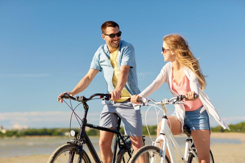 Giovani biciclette felici di guida delle coppie alla spiaggia immagine stock