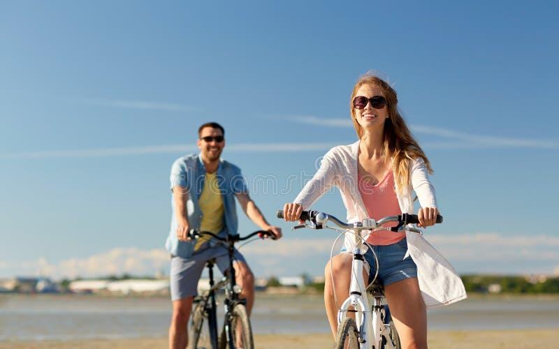 Giovani biciclette felici di guida delle coppie alla spiaggia fotografia stock
