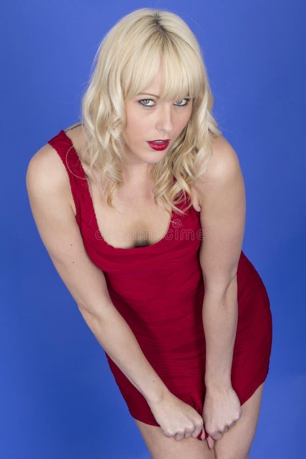 Giovani brevi rossi di Pin Up Model Posing Pulling si vestono giù fotografia stock