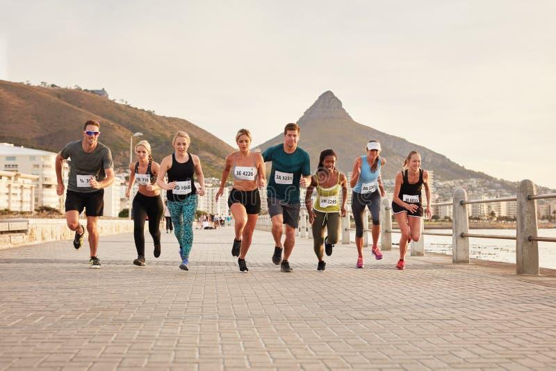 Giovani in buona salute che corrono insieme nella città immagini stock