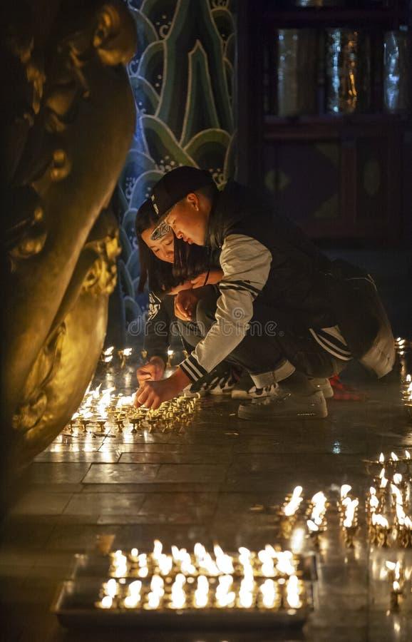 Giovani candele di illuminazione delle coppie in un tempio buddista fotografia stock libera da diritti