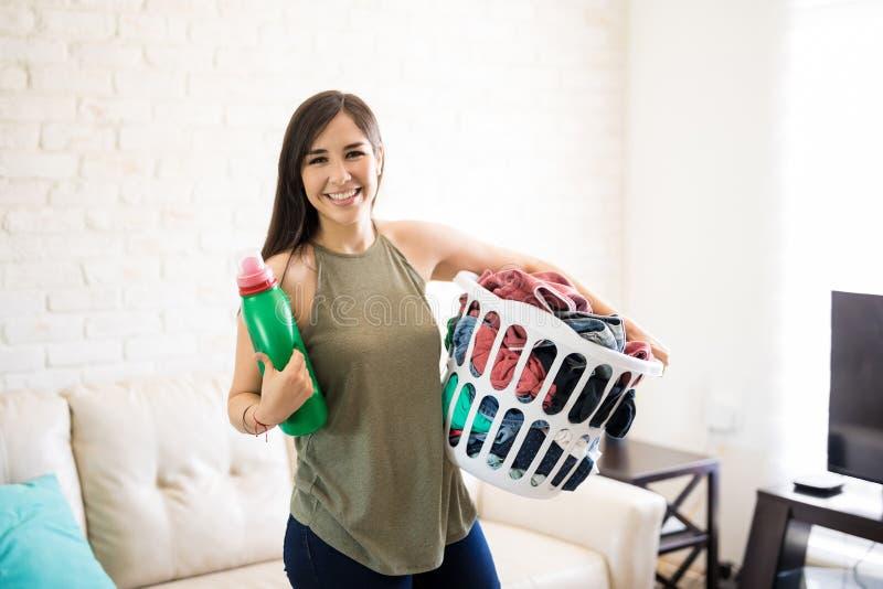 Giovani canestro e detersivo di lavanderia sorridenti della tenuta della donna fotografie stock libere da diritti