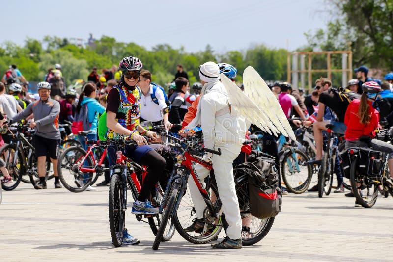 Giovani in caschi e un costume con le ali che ciclano, festival di angelo della bicicletta nella città Dnipro Giorno Dniepropetov fotografia stock libera da diritti