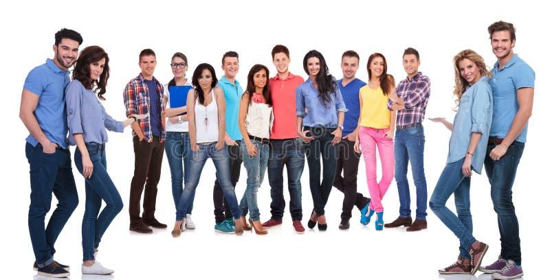 Giovani casuali che vi invitano a fare parte del loro gruppo fotografia stock
