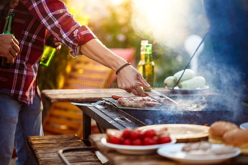 Giovani che arrostiscono barbecue sulla griglia nella campagna del cottage immagine stock libera da diritti