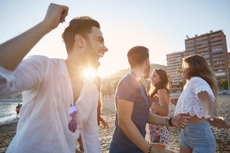 Giovani che ballano con le loro amiche sulla spiaggia fotografia stock libera da diritti