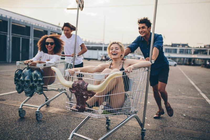 Giovani che corrono con i carrelli di acquisto immagini stock libere da diritti