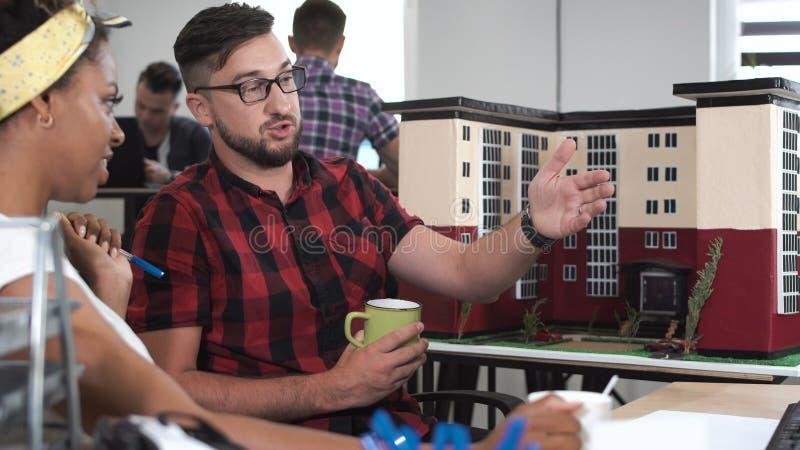 Giovani che discutono modello di nuova costruzione immagine stock libera da diritti
