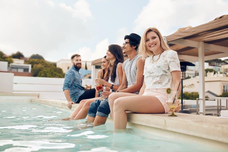 Giovani che fanno festa dal poolside fotografia stock libera da diritti
