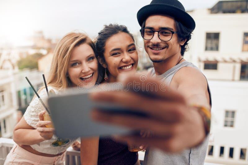 Giovani che fanno festa e che prendono selfie sul tetto fotografia stock libera da diritti