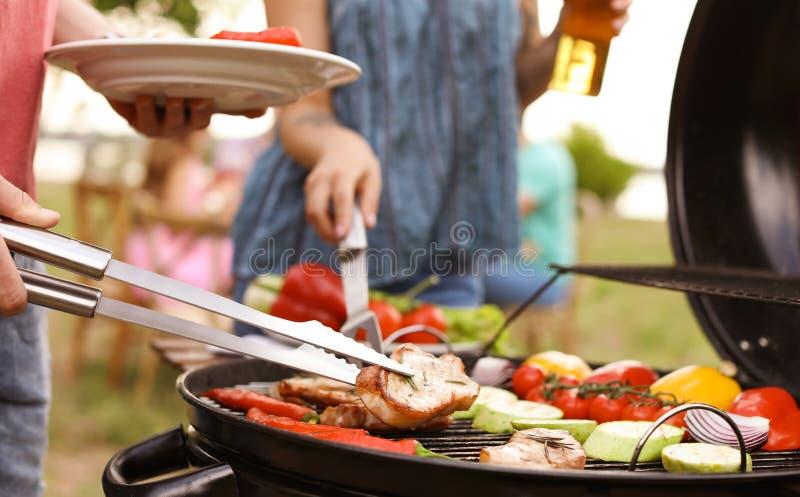 Giovani che hanno barbecue con gril moderno immagine stock