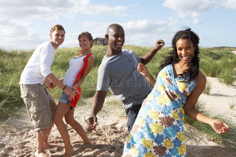 Giovani che hanno Dancing di divertimento sulla spiaggia fotografie stock libere da diritti