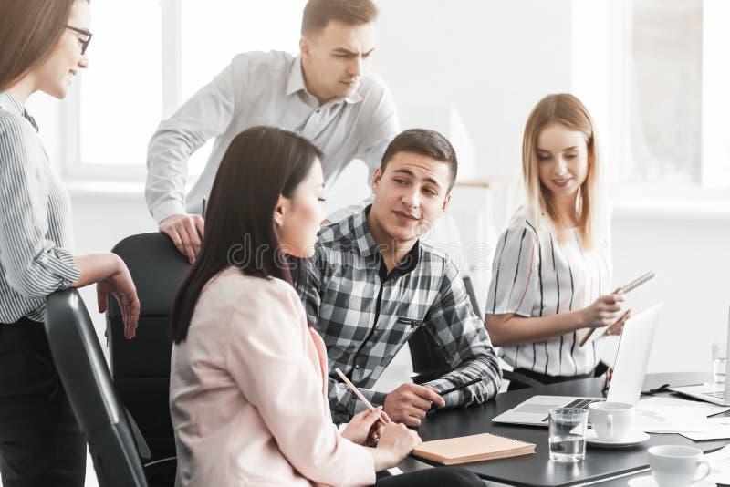 Giovani che hanno riunione d'affari in ufficio immagini stock libere da diritti