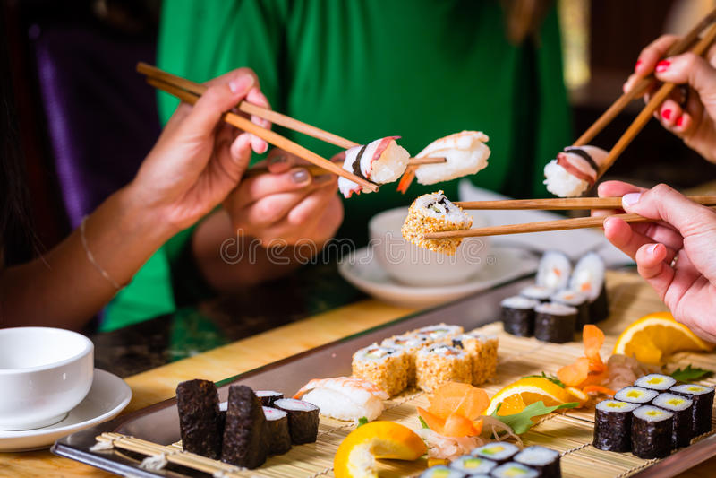 Giovani che mangiano i sushi in ristorante immagine stock