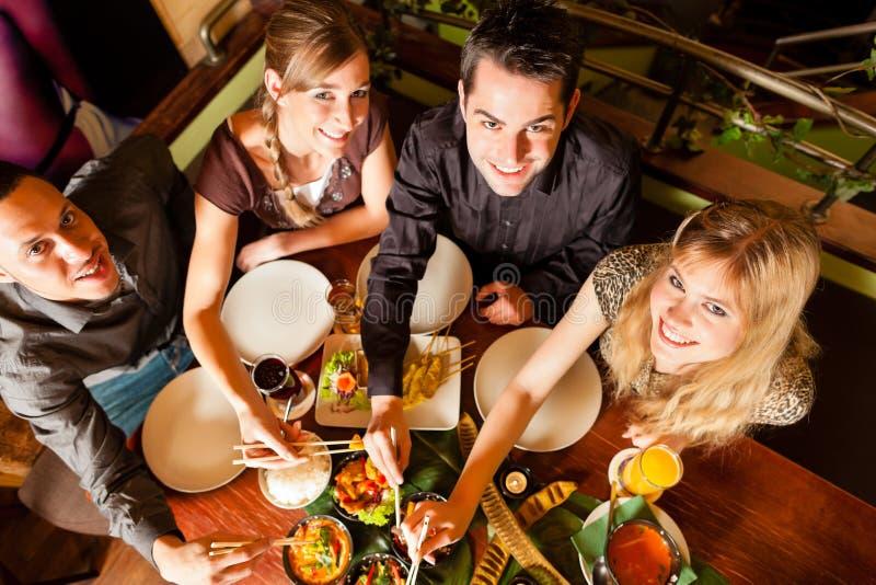 Giovani che mangiano nel ristorante tailandese immagini stock libere da diritti