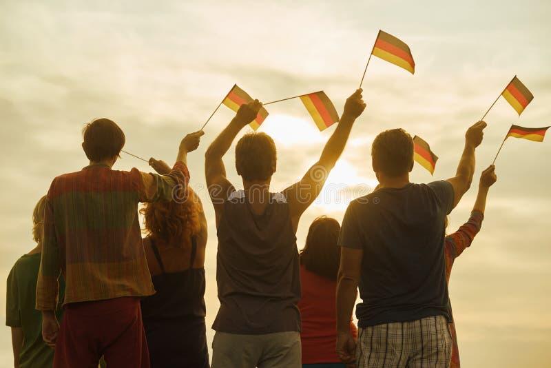 Giovani che ondeggiano le bandiere di deutsch, vista posteriore fotografia stock libera da diritti