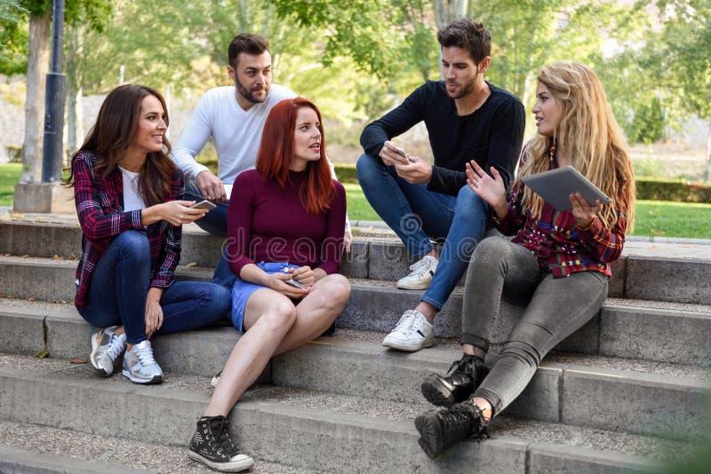 Giovani che per mezzo dei computer della compressa e dello smartphone all'aperto fotografia stock