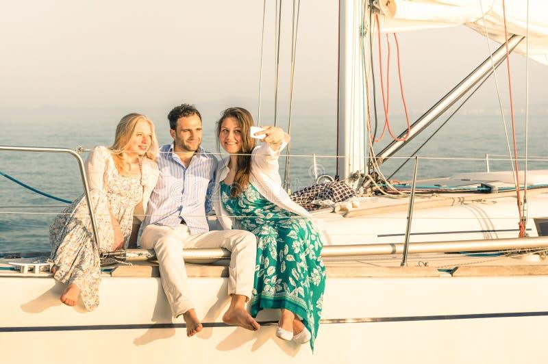 Giovani che prendono selfie sulla barca a vela di lusso esclusiva fotografie stock libere da diritti