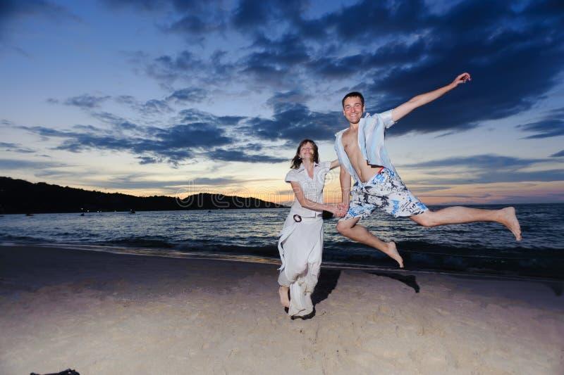 Giovani che saltano sulla spiaggia fotografia stock libera da diritti