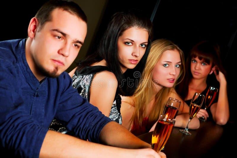 Giovani che si distendono in una barra. fotografia stock