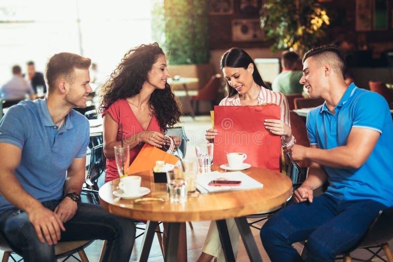 Giovani che si incontrano in un caffè dopo la compera fotografie stock