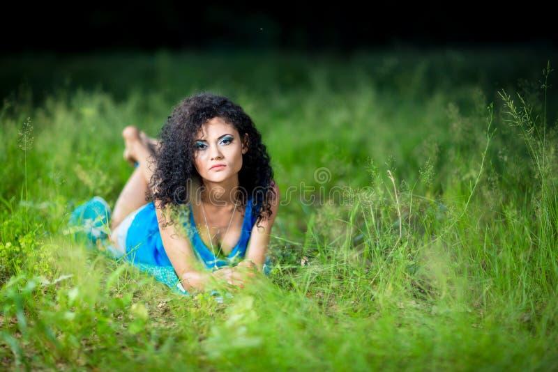 Giovani che si rilassano menzogne femminile sul suo stomaco nell'erba fotografia stock