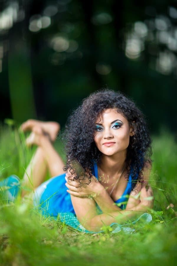 Giovani che si rilassano menzogne femminile sul suo stomaco nell'erba fotografia stock libera da diritti