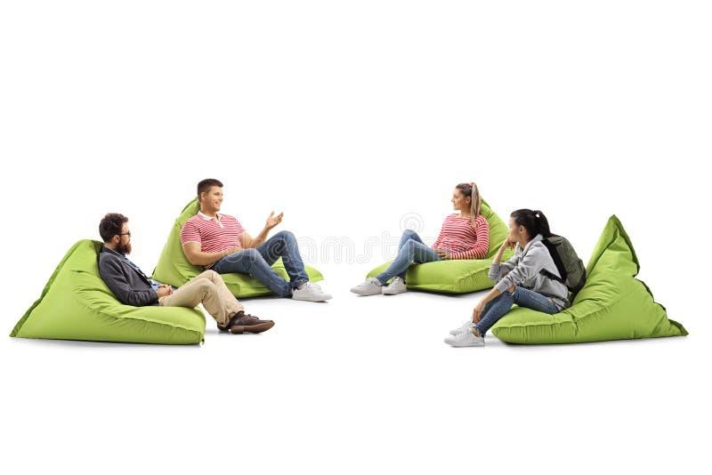 Giovani che si siedono sulle borse di fagiolo e che hanno una conversazione fotografia stock libera da diritti