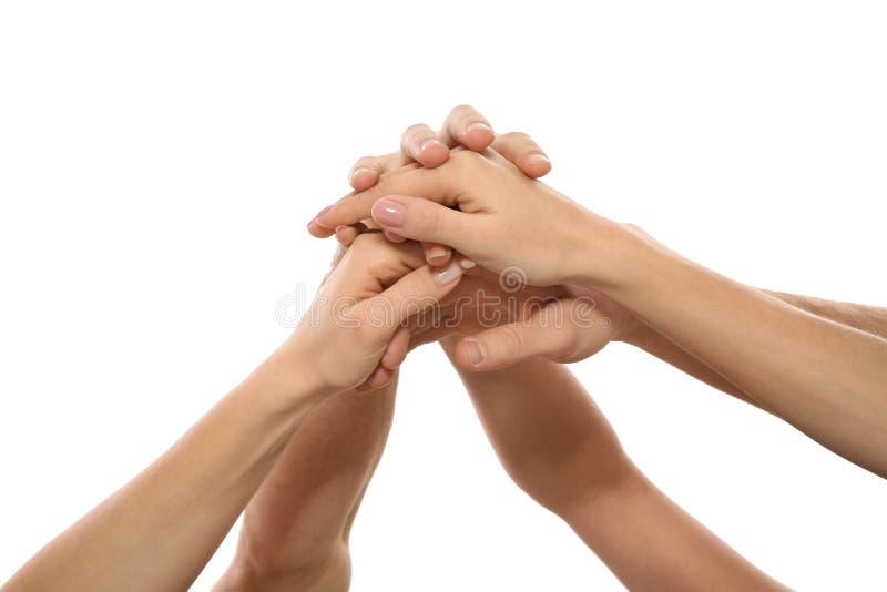 Giovani che si tengono per mano insieme su bianco, primo piano Concetto di vittoria del gruppo immagini stock