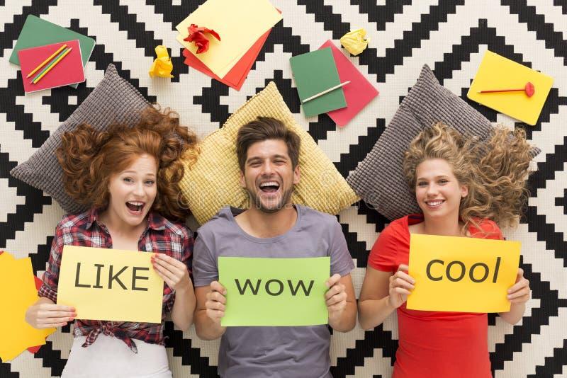 Giovani che si trovano sul tappeto e sulla risata immagini stock libere da diritti